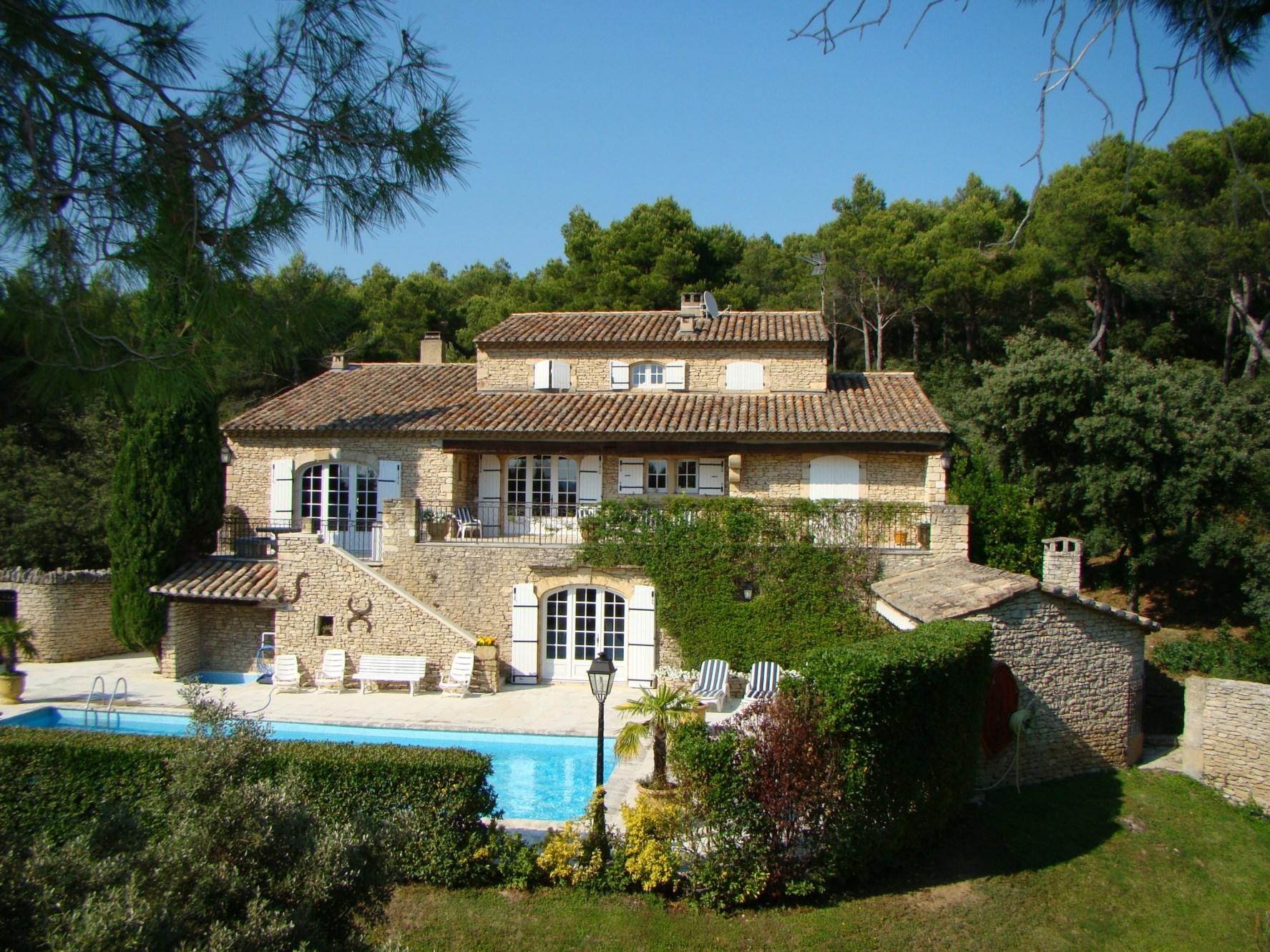 A quelques minutes du village de Gordes, en position dominante et bénéficiant de vues sur le Luberon et les Alpilles, maison de charme en pierres totalement rénovée à vendre, grande maison en pierres traditionnelle,  avec un parc d'un hectare et piscine