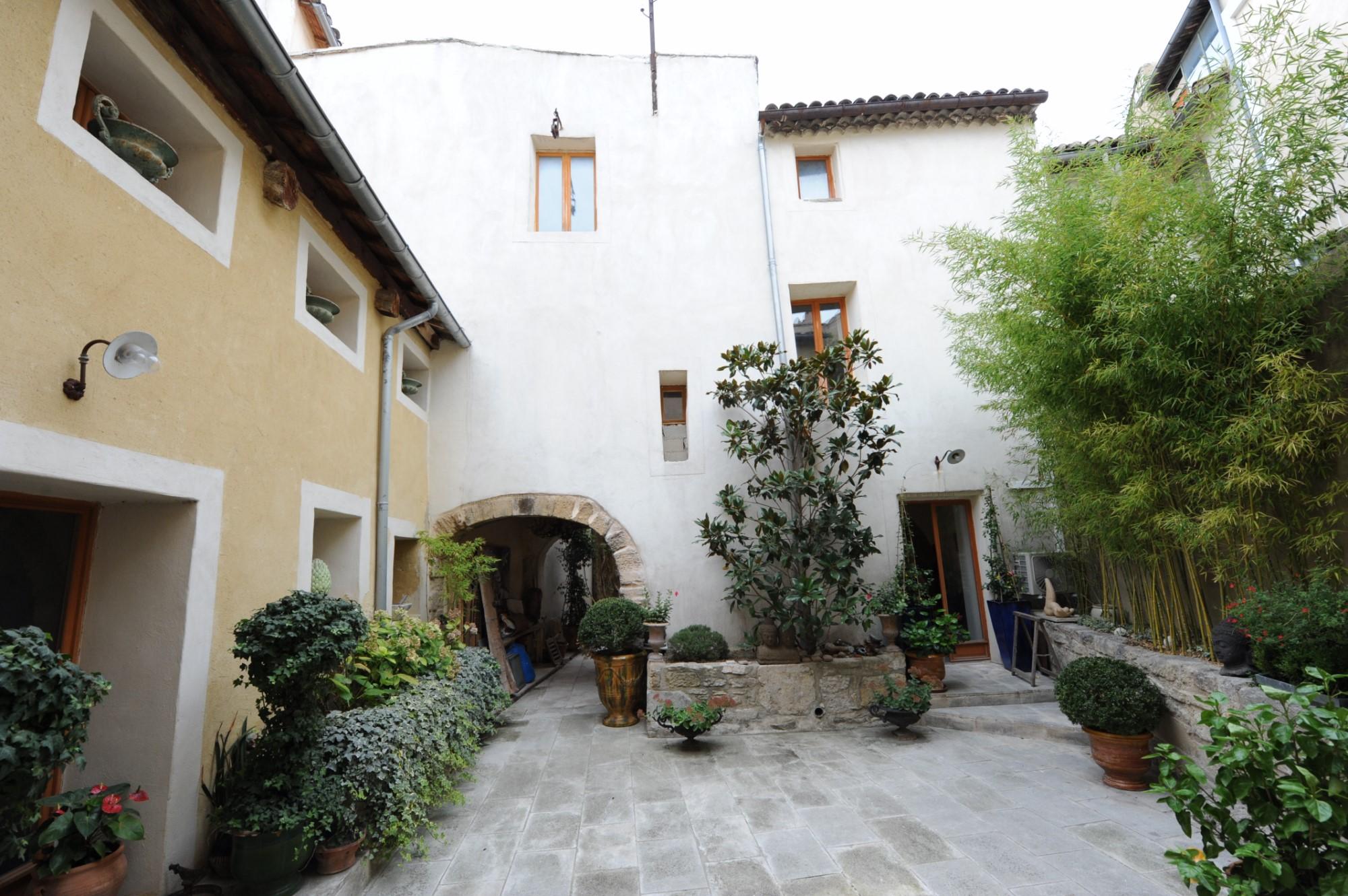 A vendre, à l'Isle sur la Sorgue,  ensemble immobilier avec une maison d'habitation,  2 appartements, un local commercial et un beau patio.