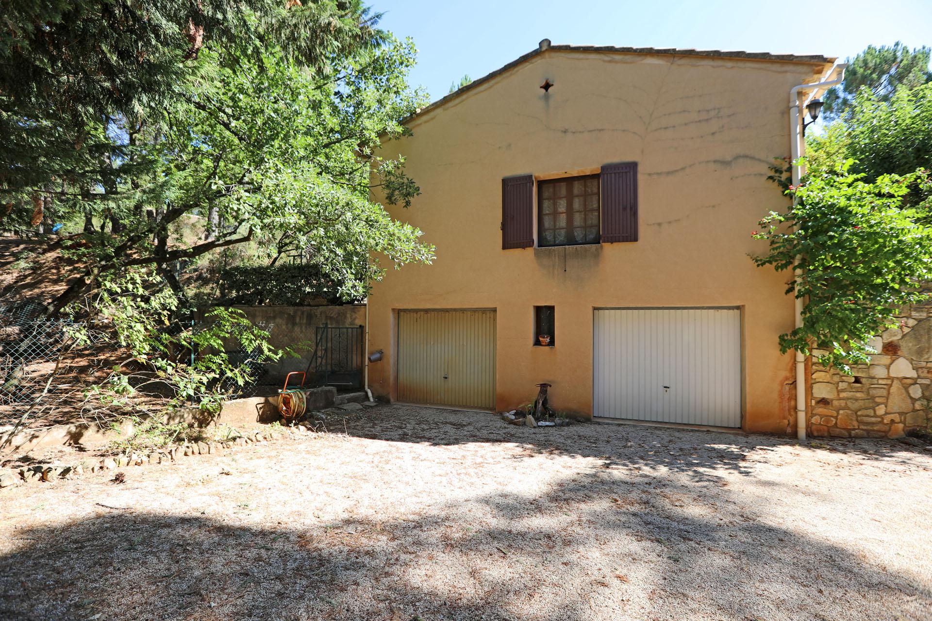 Les garages en contrebas de cette maison à vendre à Roussillon